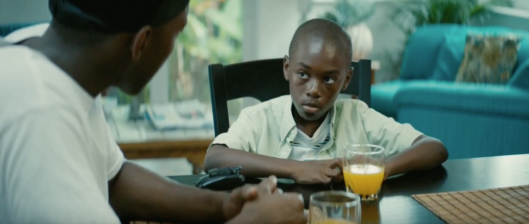A young boy is sitting at the table quietly drinking juice.
