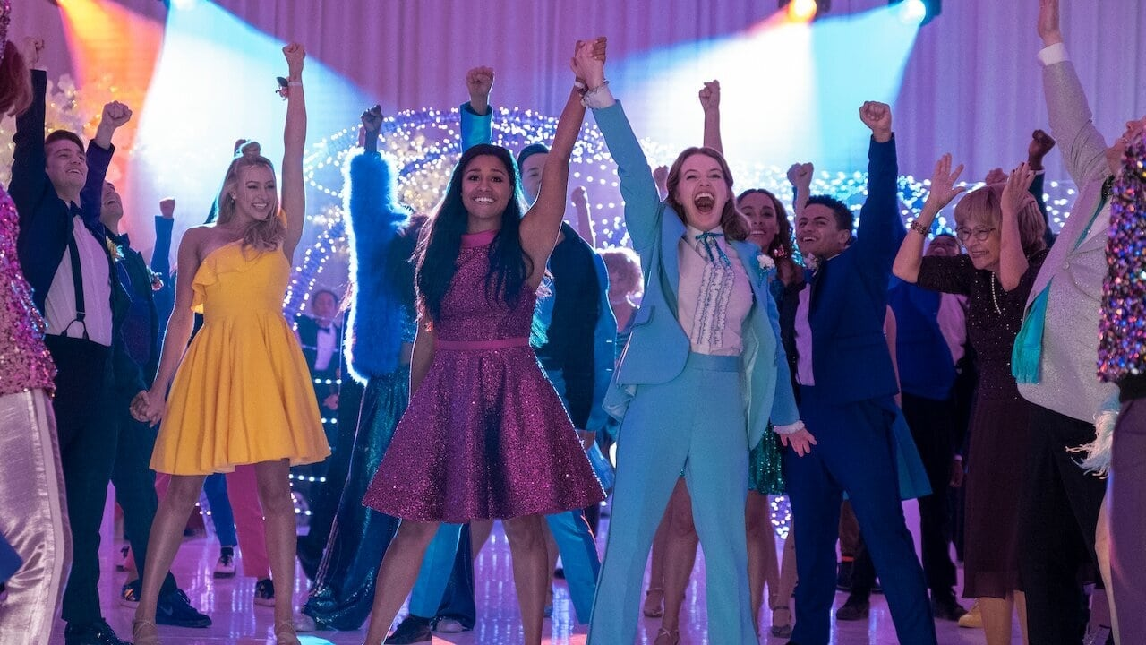 Emma and her girlfriend Alyssa triumphantly raise their joined hands at the prom.