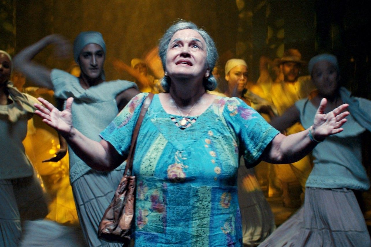 Abuela Cluadio, an older woman with grey hair and a blue dress, stands in front of a group of female dancers. Her arms are open and she looks to to the sky.