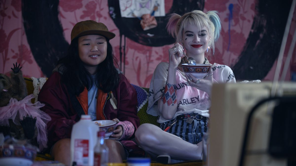 Cassandra Cain and Harley Quinn eat ceral together on a couch.
