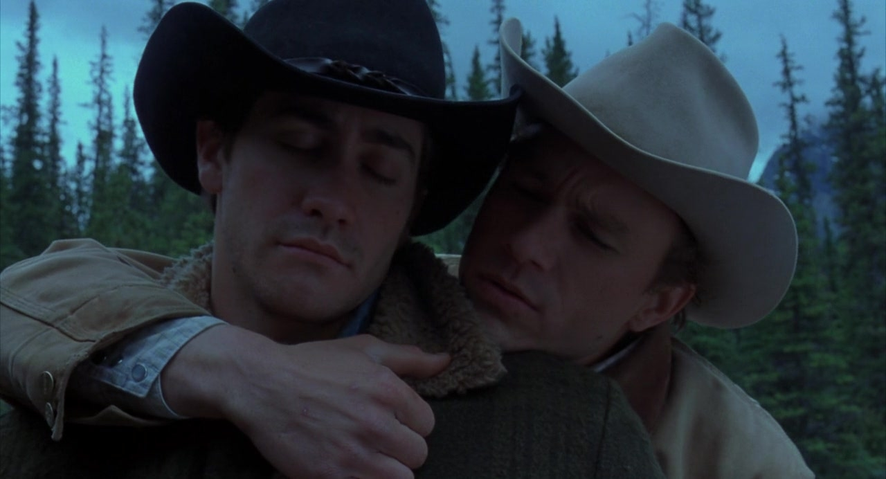 Ennis (Heath Ledger) embraces Jack (Jake Gyllenhal) from behind. Both wear cowboy hats and have their eyes closed. A forest is behind them.