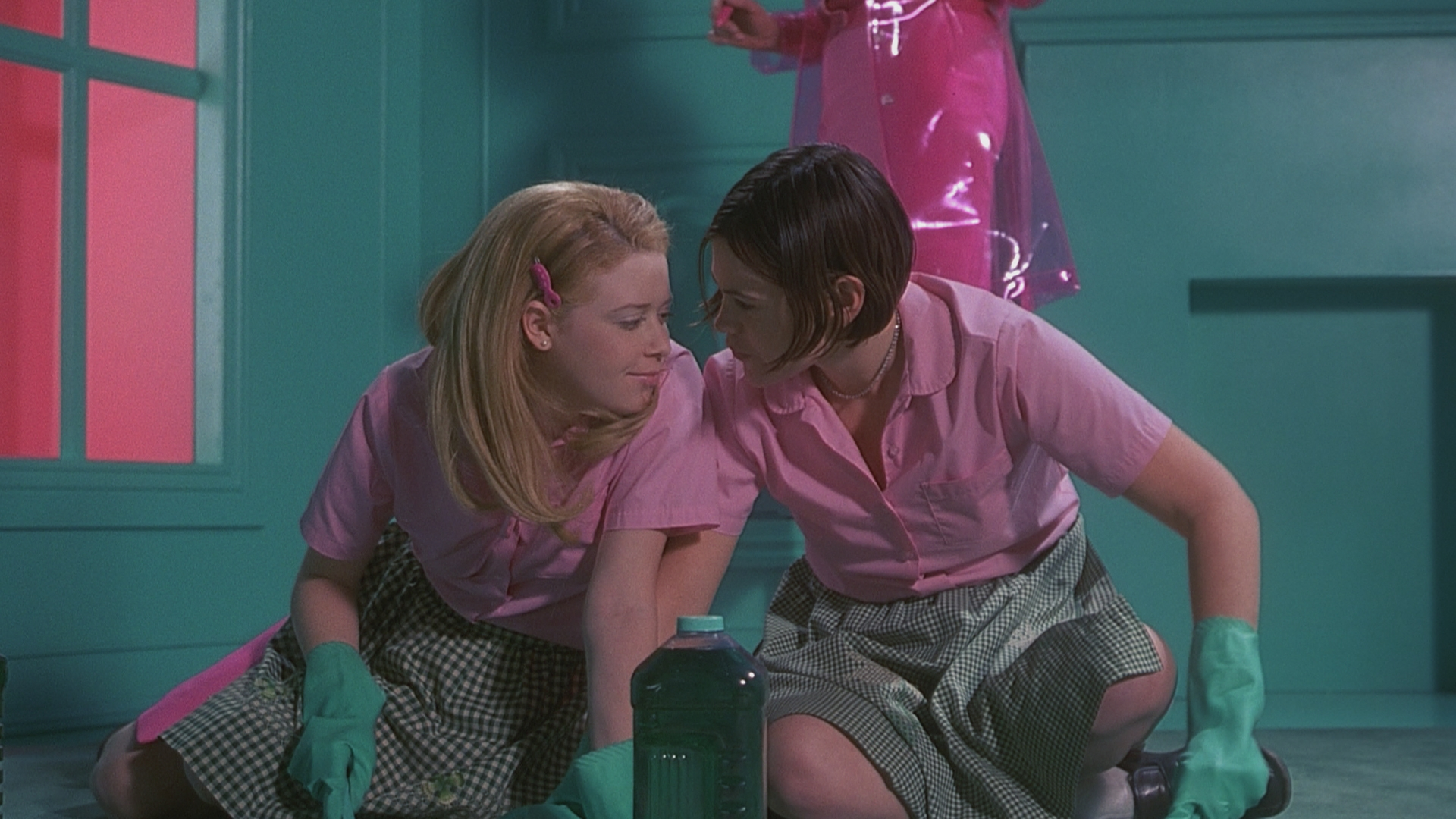Megan and Graham take a break from scrubbing the floor to stare into each other's eyes. Both are wearing pink uniforms and rubber gloves.