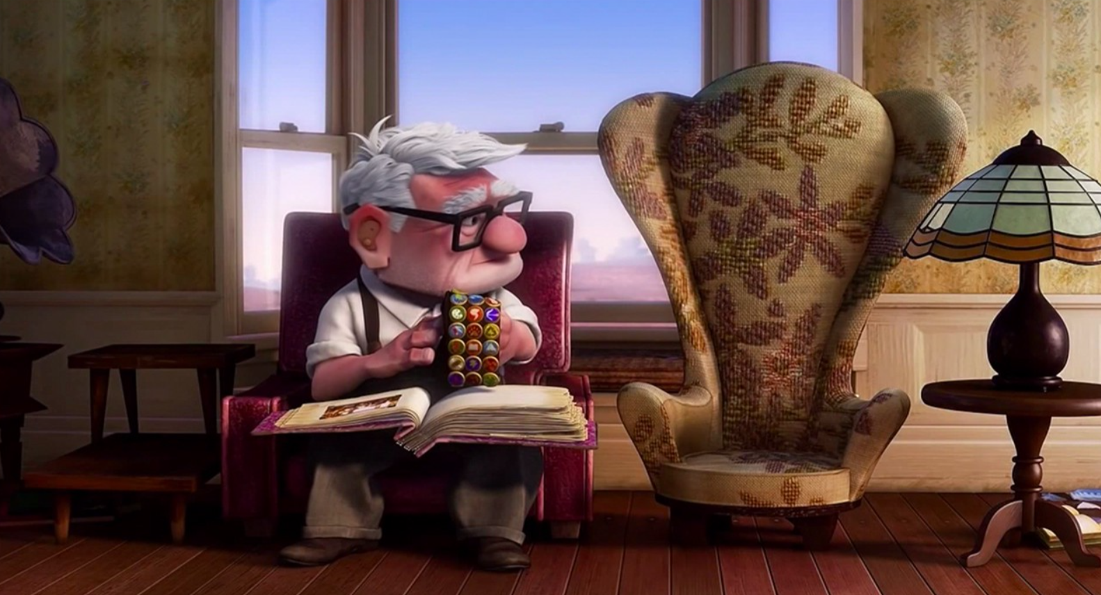 Carl sits in his armchair with a scrapbook open on his lap. He holds Russell's scout sash and looks at Ellie's empty armchair next to him.