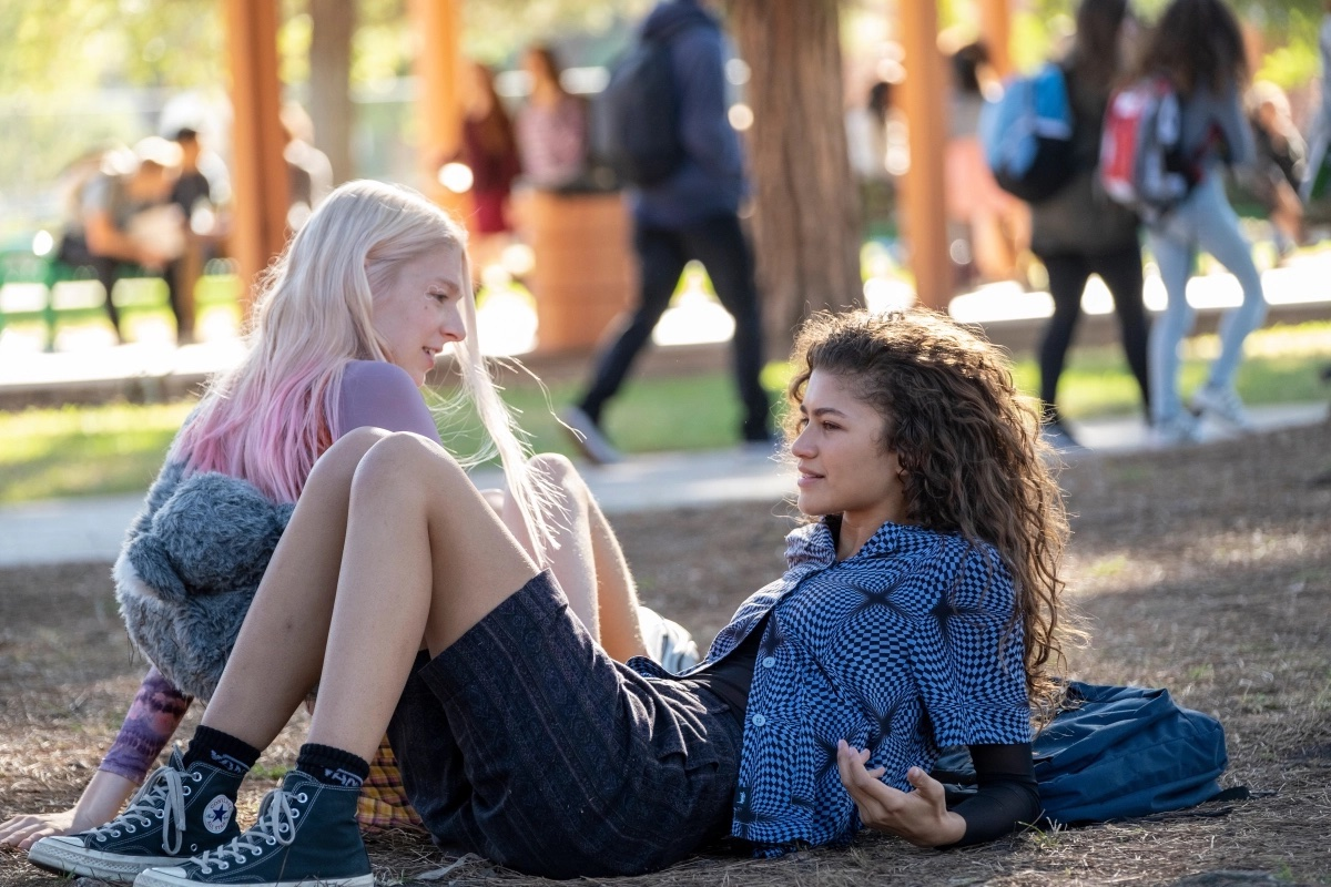 Jules (Hunter Schafer) and Rue (Zendaya) relax and chat in a park.