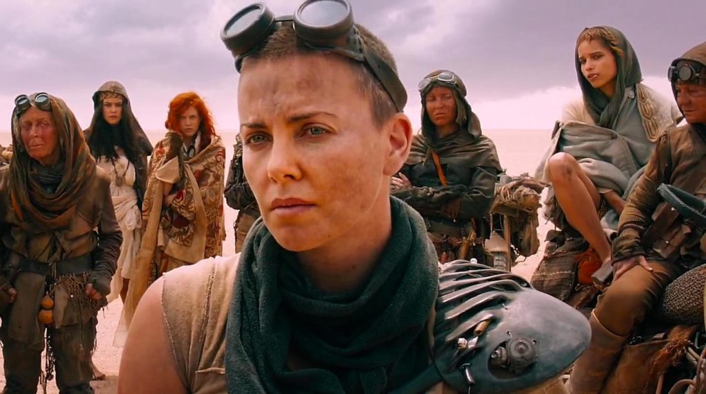 Furiosa (Charlize Theron) stands in the foreground with a pair of goggles on her forehead. A group of women stand behind her. In the background, a vast desert and a cloudy sky.