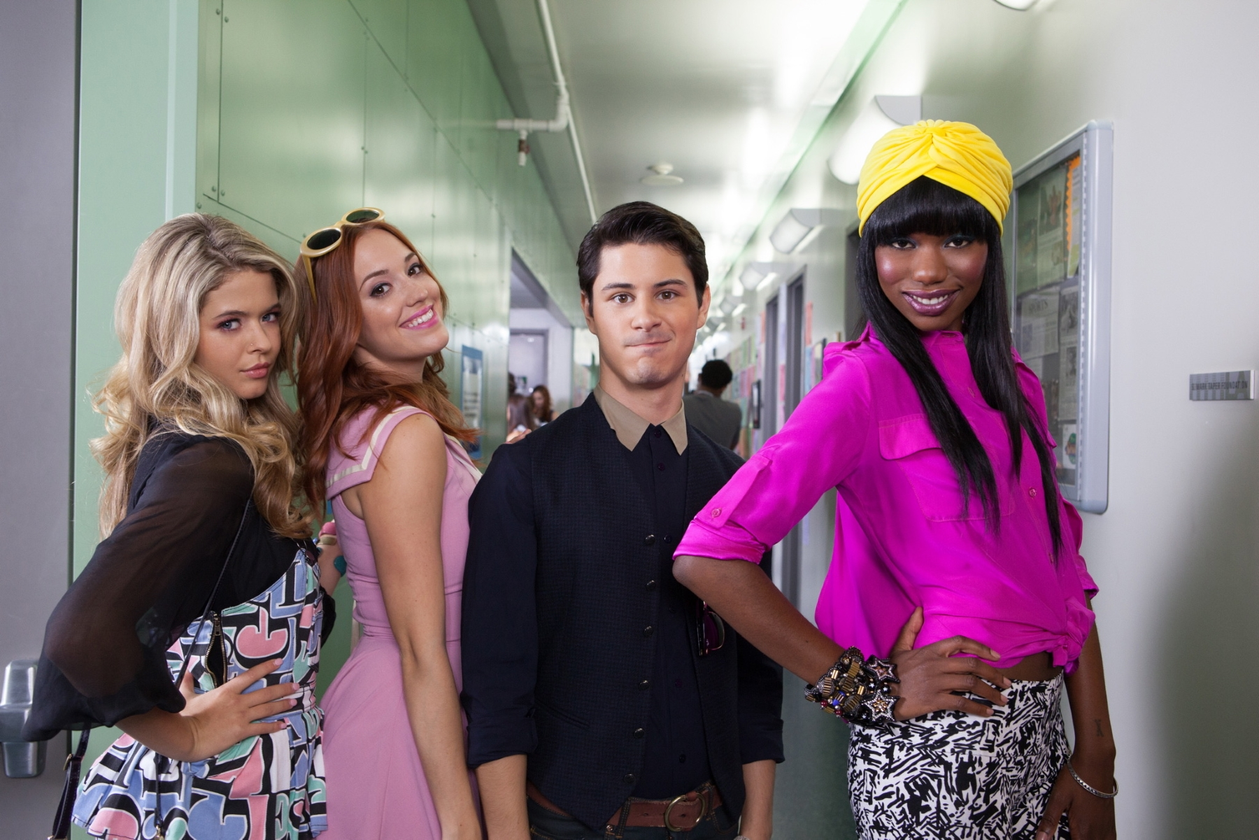 Michael, flanked by three high school girls, standing in a school hallway. The girls are all smiling, while he looks uncomfortable.