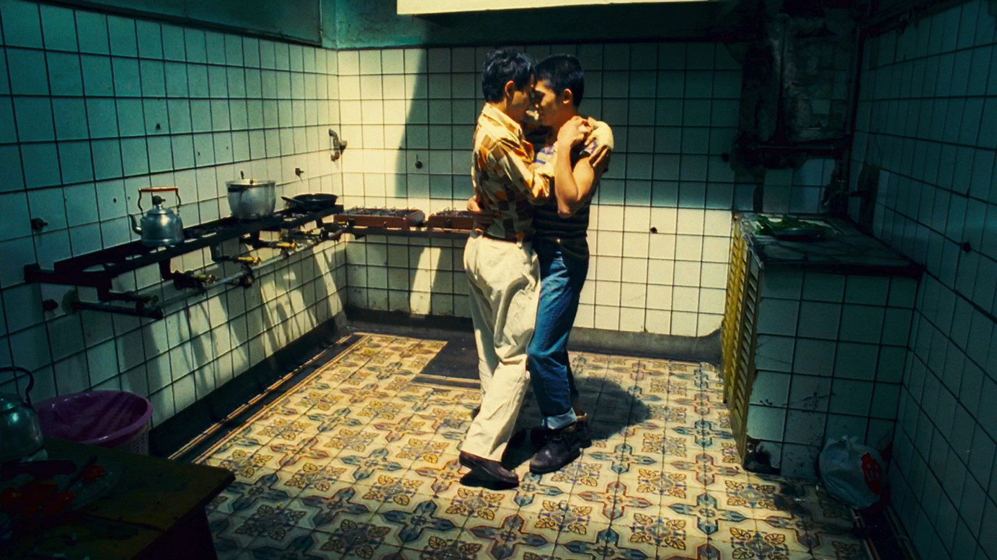 Two men slow-dance in a somewhat dilapidated kitchen.