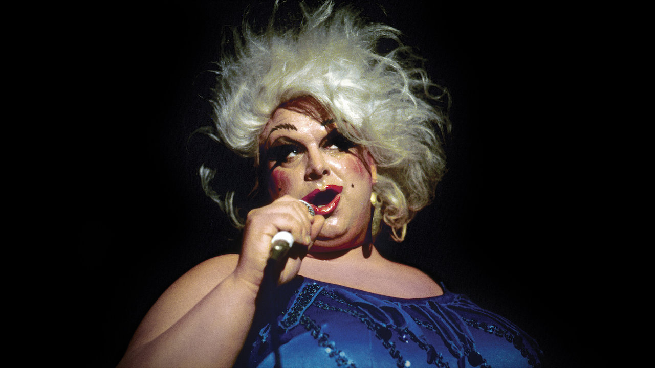 Divine, a drag queen wearing exaggerated makeup and a blue dress, speaks into a microphone.