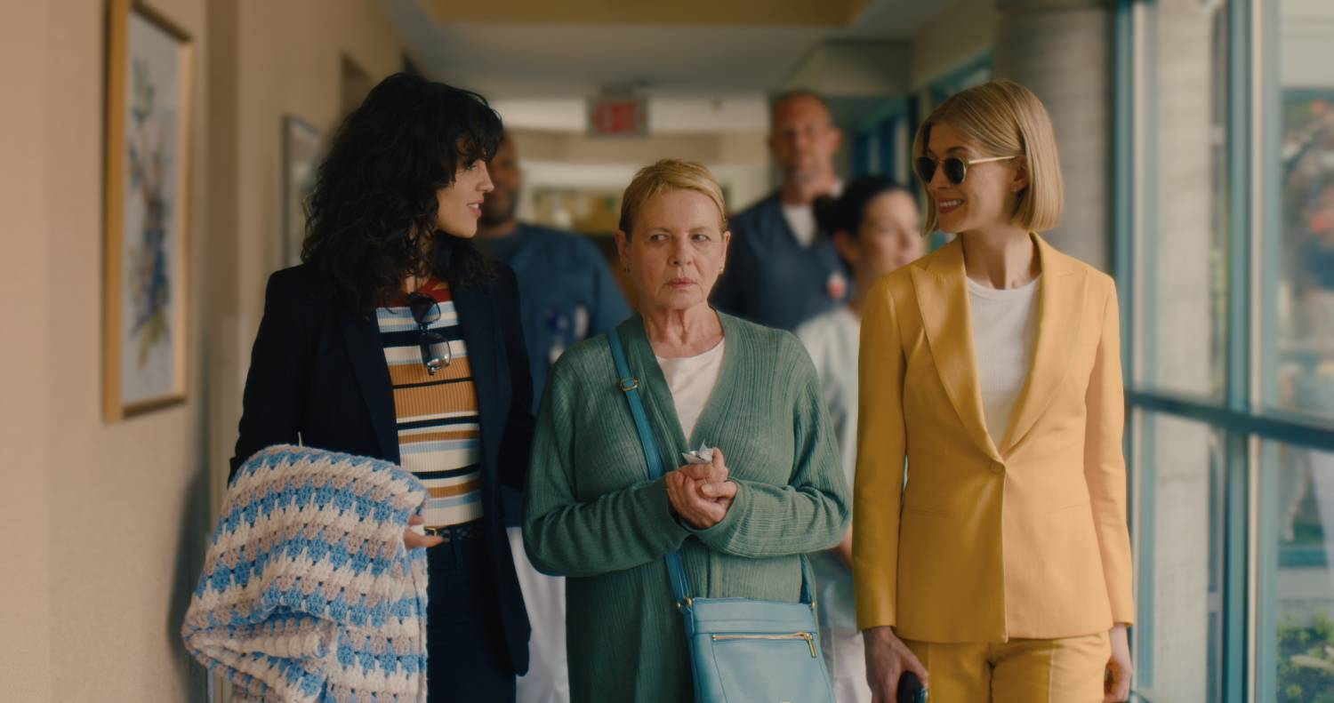 Marla and Fran (two young women) walk Jennifer (an older woman) down a hallway. Marla and Fran are smiling, and Jennifer looks suspicious.