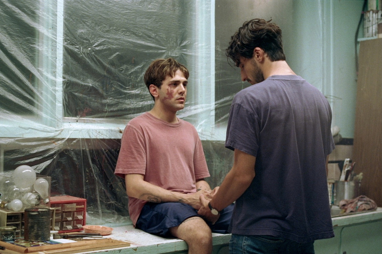 Maxime sits on a couch with a wound on his face. Matthias kneels in front of him, holding his hands.