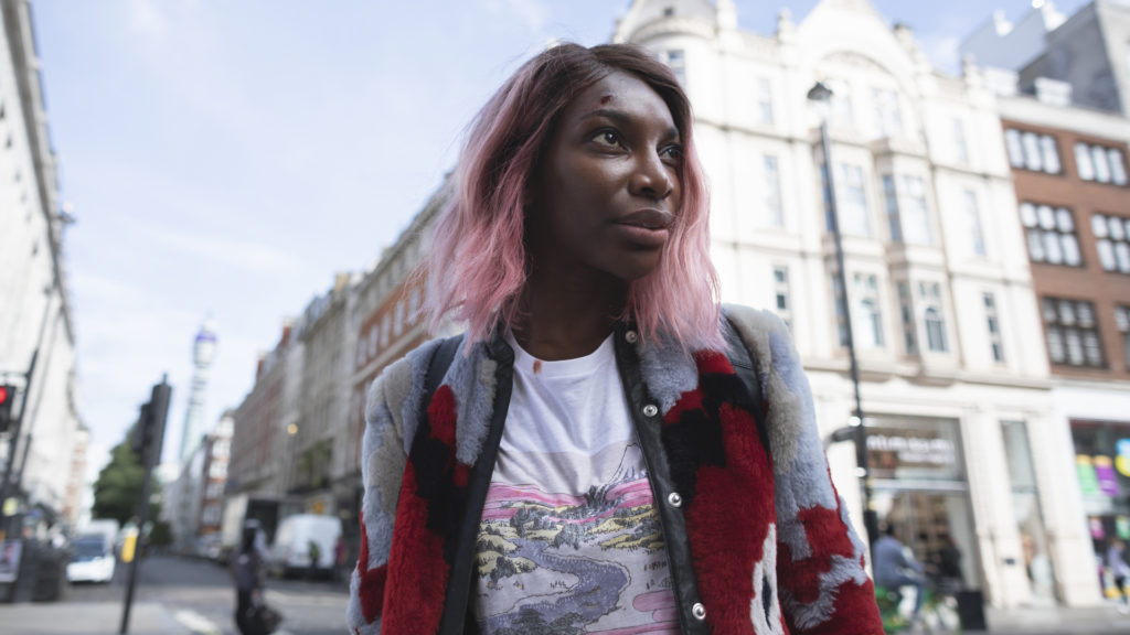 Arabella (Michaela Coel) walks down a city street. She has a small cut on her forehead and a bloodstain on her shirt.