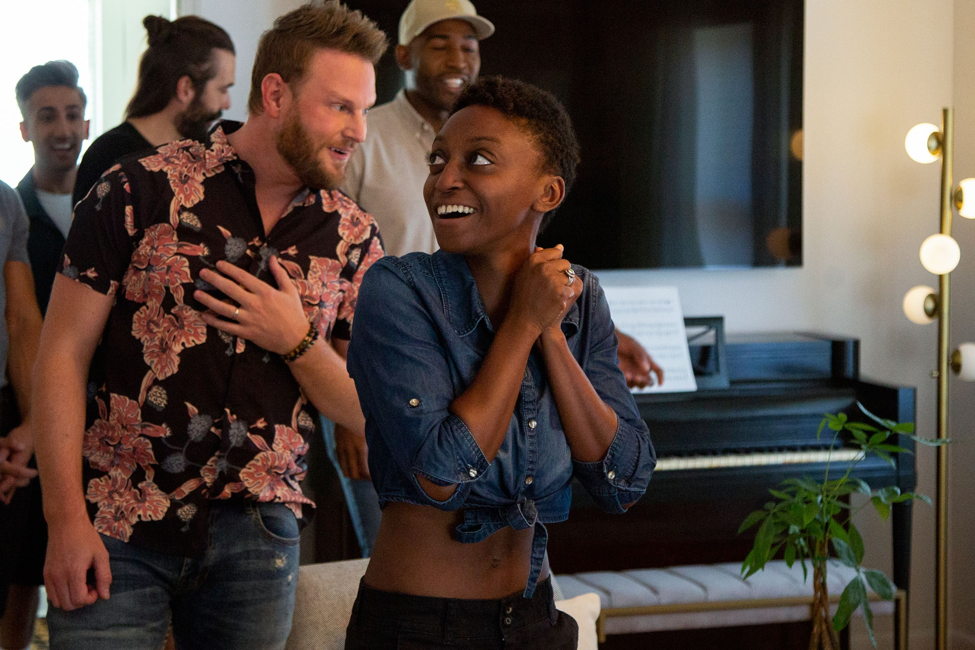 Queer Eye hero Jess reacts with surprise and delight to her remodeled home. The Fab Five follow her into the room.