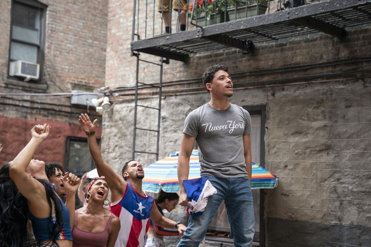 """Usanavi stands above a cheering crowd. He wears a T-shirt that reads """"Nuevo York"""" and holds a crumpled flag in one hand."""