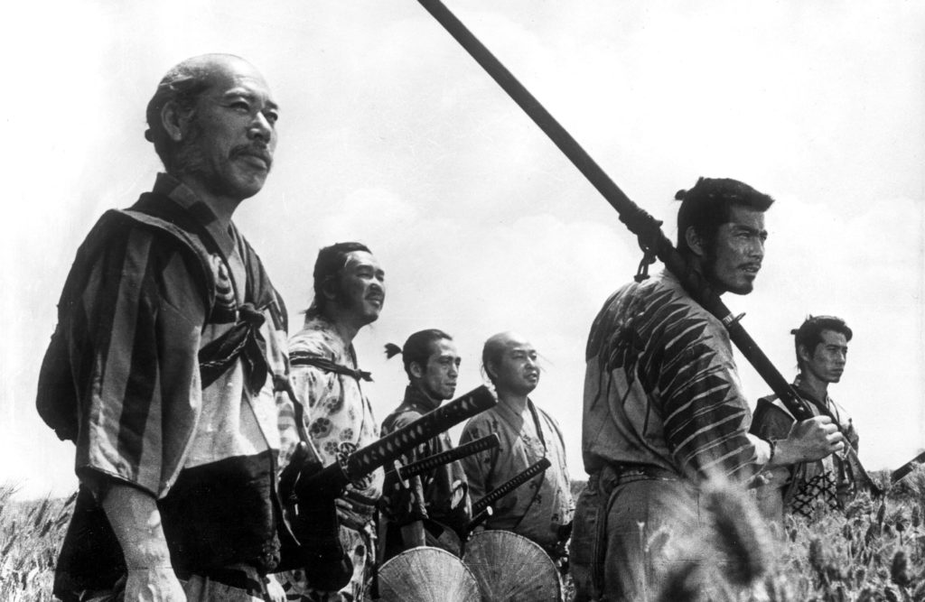 The seven samurai stand in a field. Kambei (Takashi Shimura) and Kikuchiyo (Toshiro Mifune) are in the foreground of the image. Kambei has a slight smile on his face, and Kikuchiyo holds an enormous katana over his shoulder.