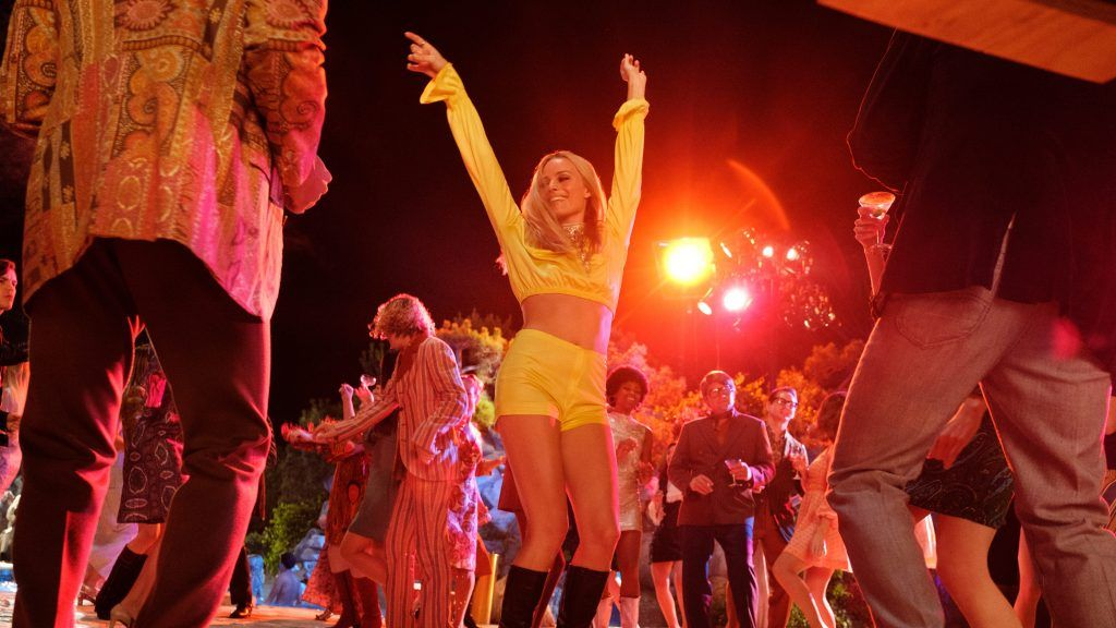 Margot Robbie as Sharon Tate, dancing at an outdoor party.