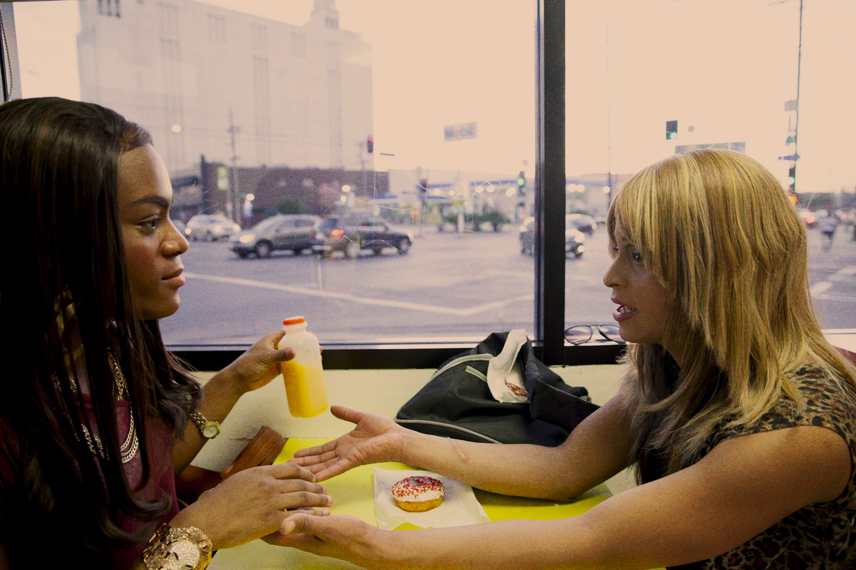 Alexandra and Sin-Dee (two trans women) hold hands over the table at a diner.
