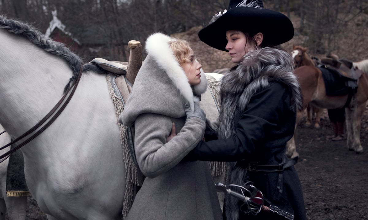 Kristina, wearing a furred jacket and a jaunty hat, helps Countess Ebba onto a horse.