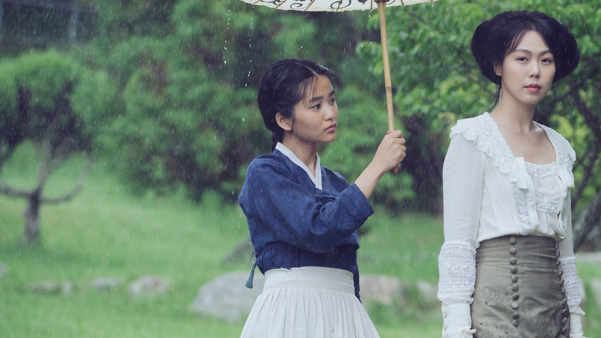 Sook-hee holds a parasol over Izumi's head.