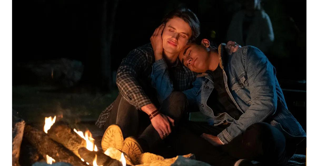 A still of Victor and Benji sitting together at a campfire