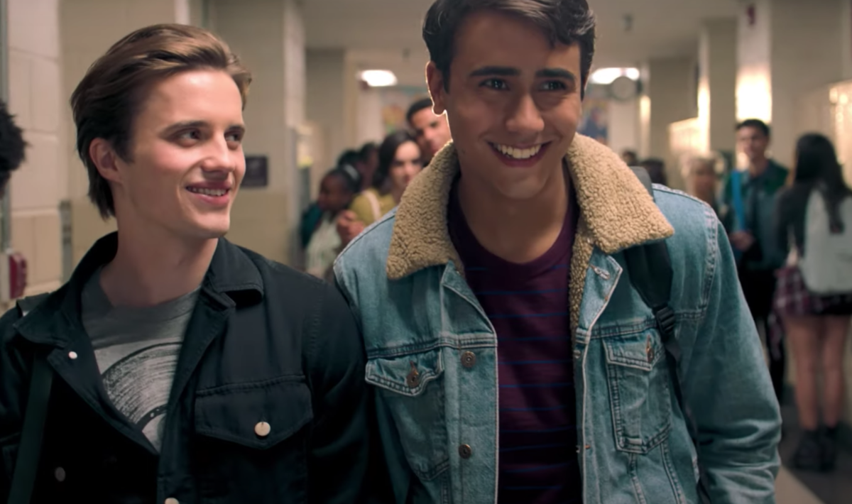 A still of Victor and Benji smiling as they walk through the school hallways