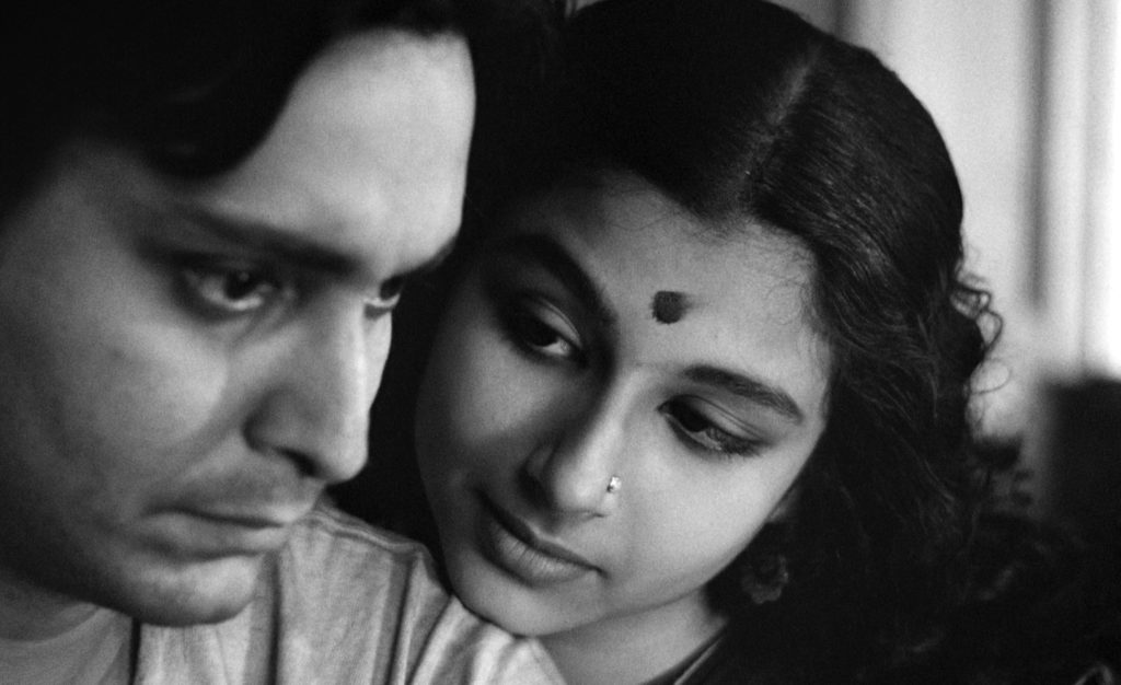 Aparna (Sharmila Tagore), a woman with a nose piercing and a bindi, rests her head on her husband Apu's shoulder. Apu (Soumitra Chatterjee) has a somber look on his face.