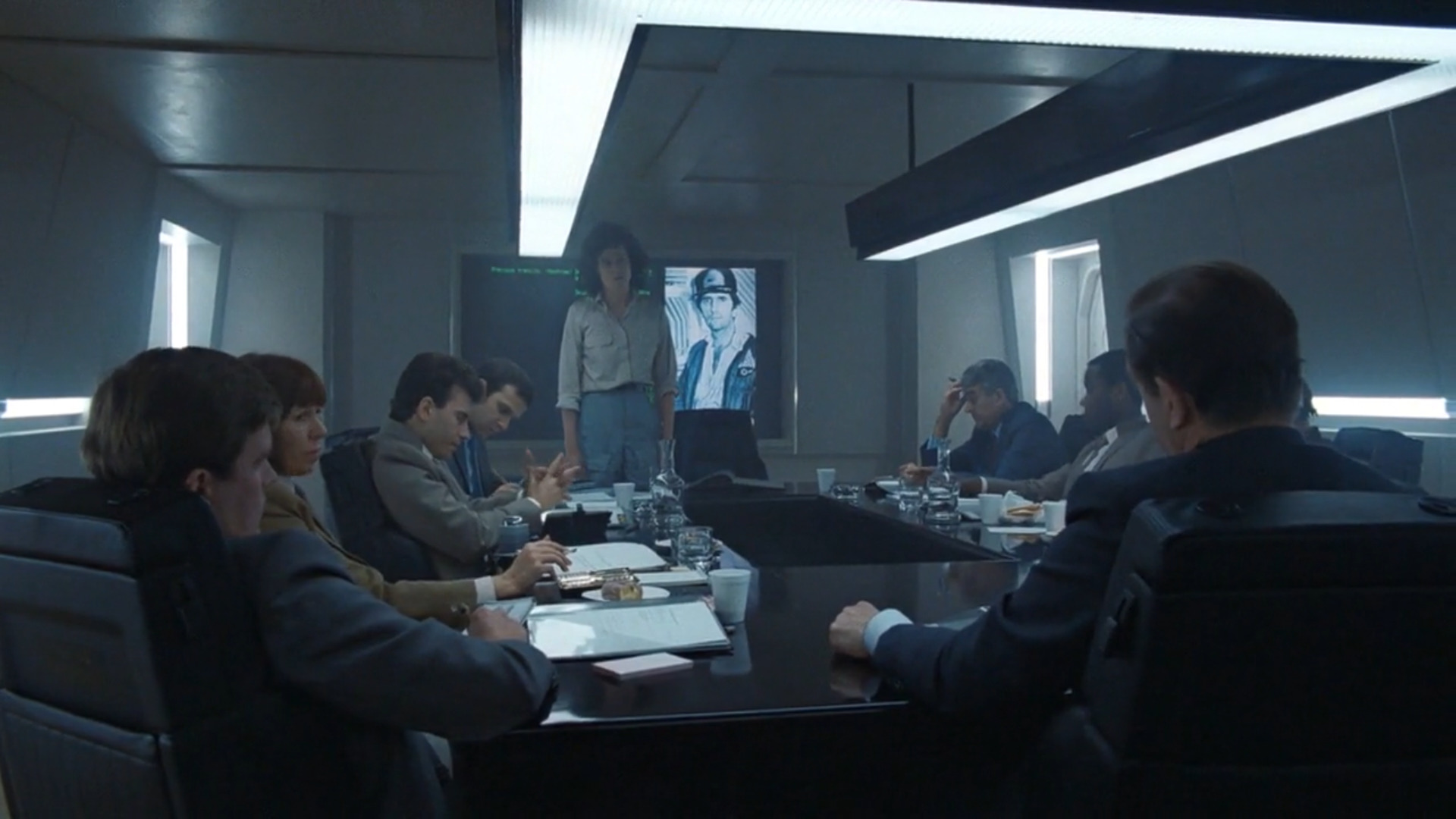 Ripley (Sigourney Weaver) faces a debriefing after being rescued from hypersleep, but is ultimately dissatisfied that her employers do not believe her story about the presence of the Xenomorph.