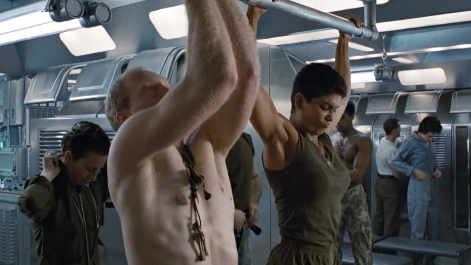 Pvt. Vasquez (Jenette Goldstein) shows off in front of her male counterparts while the Sulaco crew makes fun of Ripley from afar.