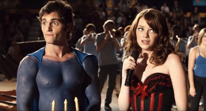 Olive and Woddchuck are at a school pep rally. They both look out at the crowd awkwardly as the lights shine on them. She is holding a mic and wearing a corset. He is painted to match the school colors.