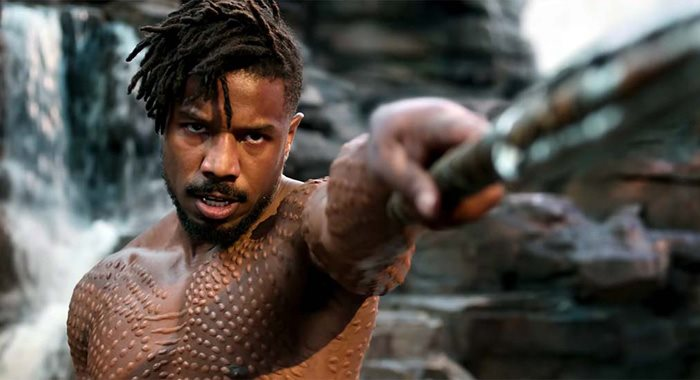 A Black man scowls and points a spear at the camera. He is shirtless, revealing many scars.