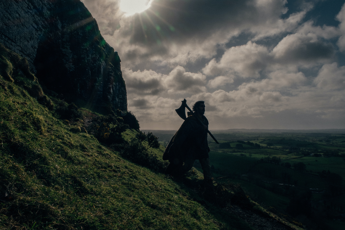 Large shot of the sky and the mountain side. Gawain is walking downward with an axe in his hand.