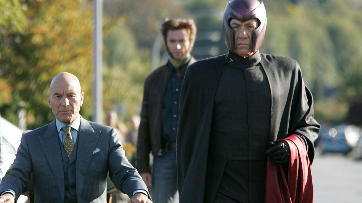 A bald man in a wheelchair and an old man in a cape and helmet walk towards the camera, followed by a man with spiky hair.