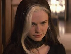 A young white woman is seen in portrait. She has long dark hair with a stark white streak in the front.