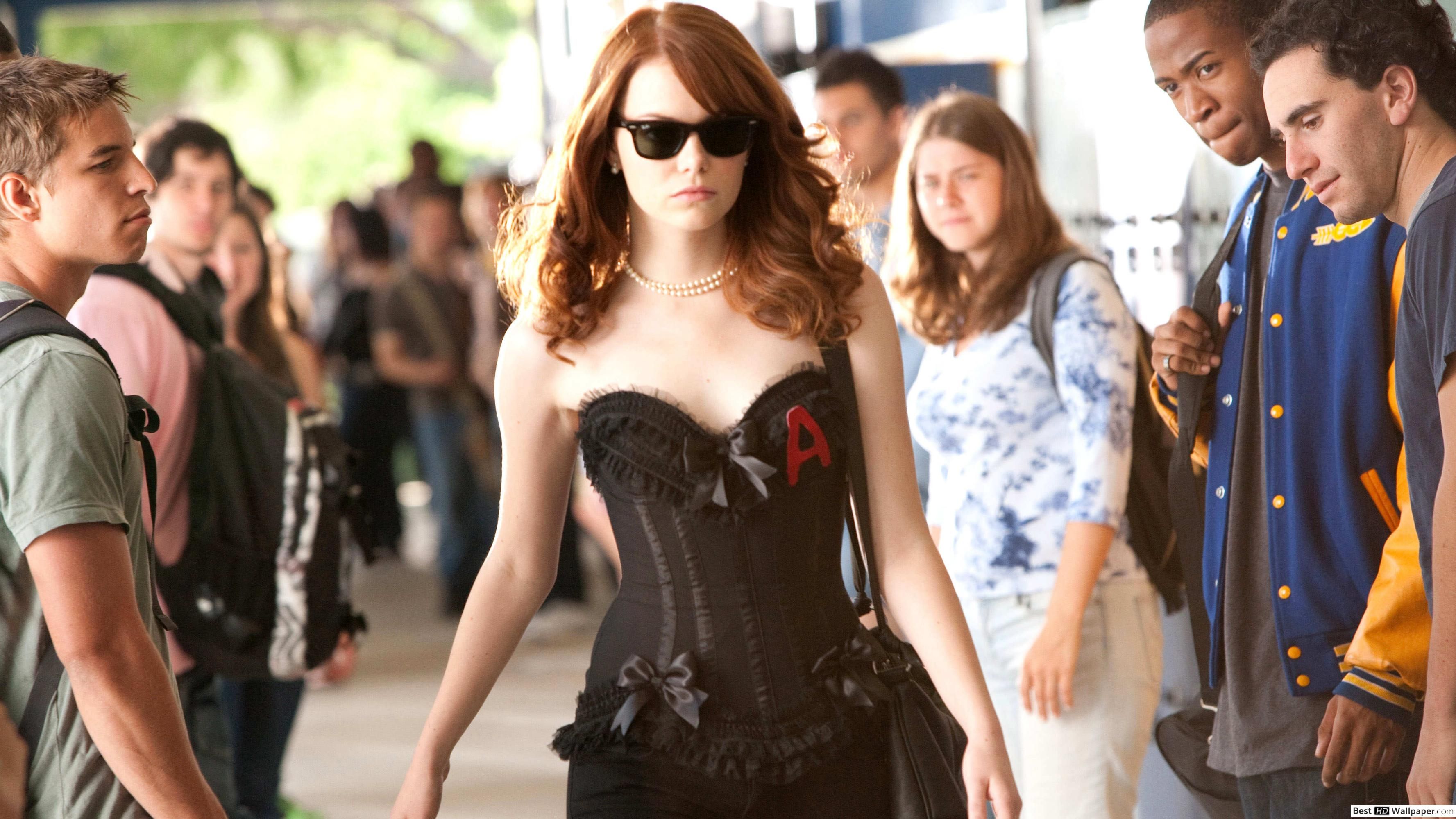 Olive walks down the outdoor hall of her school. She is wearing a corset top with the letter A on her right chest. Everyone stares at her as she walks by, and she smirks toward them all.