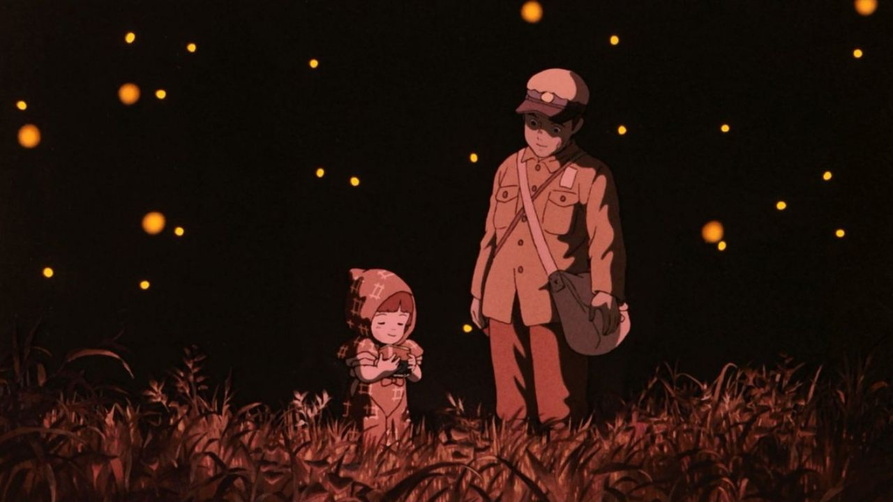 Setsuko and Seita standing in a field together with soft red lighting. They are surrounded by fireflies.