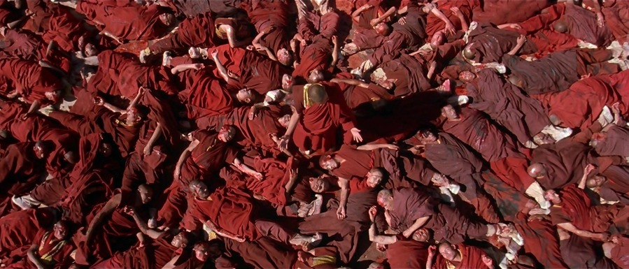 Tibetan monks wearing red robes, laying dead on the ground, Dalai Lama stands in center