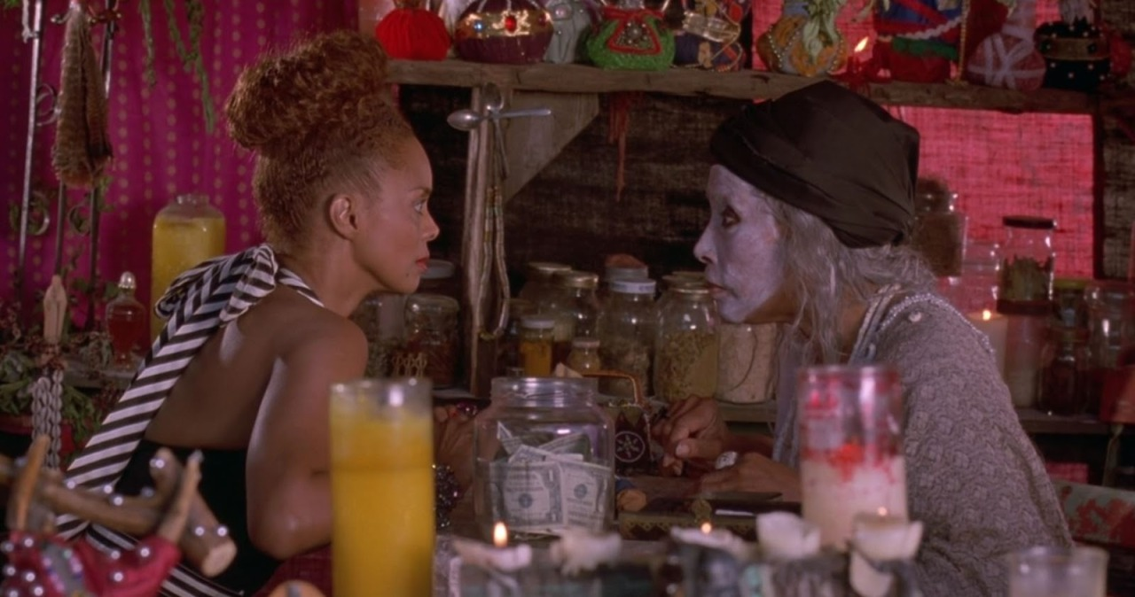 In a tent surronded by antique jars, Mozelle and Elzora sitting across from each other