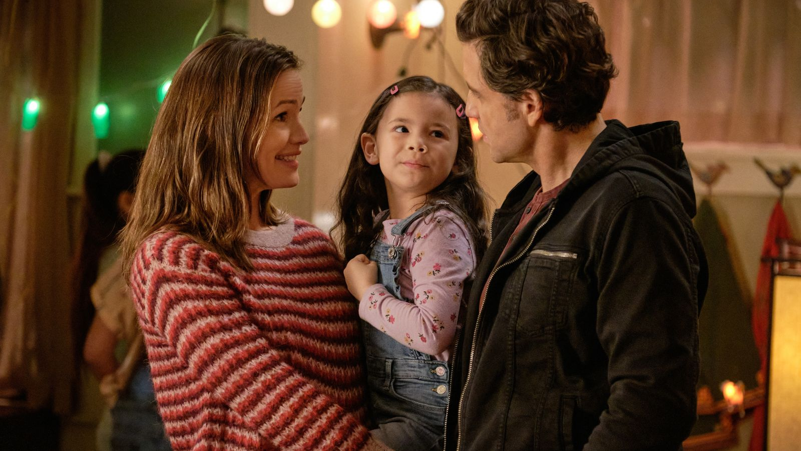 """Still from """"Yes Day"""". Allison holds her daughter while speaking to Carlos."""