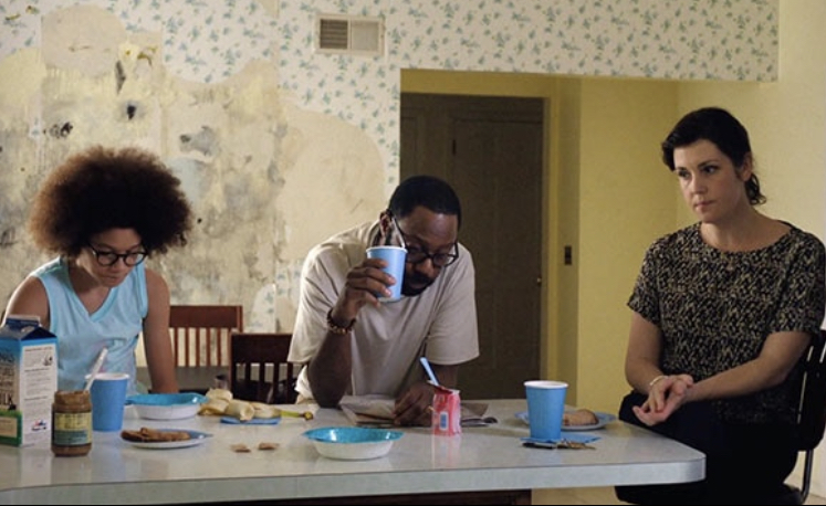 The Burns family sitting at the kitchen table for breakfast. There is friction between them all, shown by their expressions. Black mold is exposed beneath the wallpaper behind them.