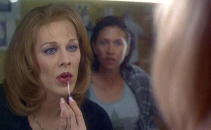 Judy applying lipstick in the mirror as her soon-to-be attacker leers at her.