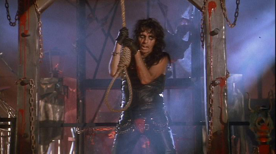 Alice Cooper holding a noose, by a gothic execution set