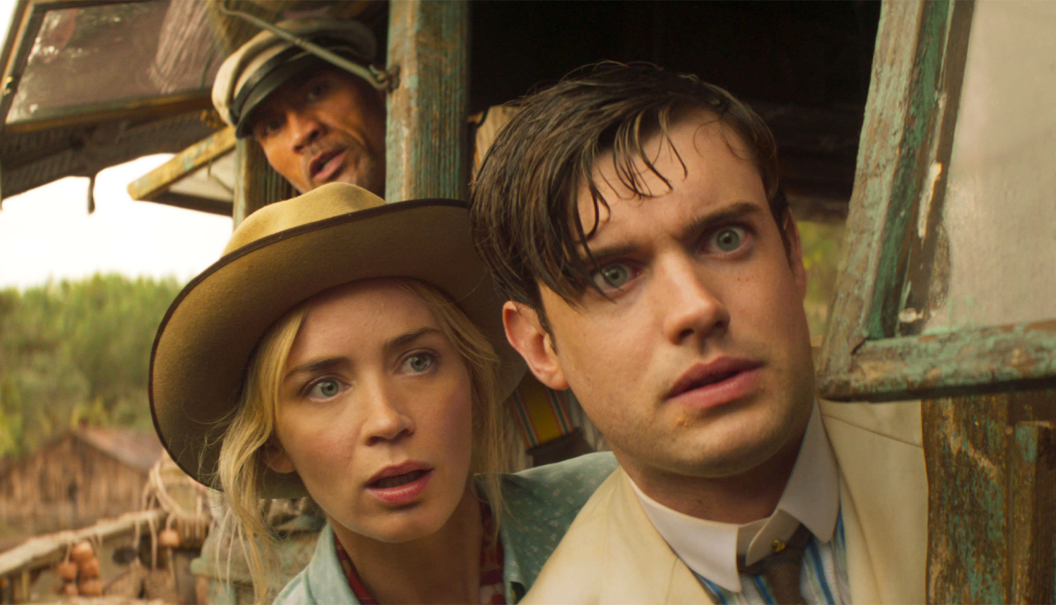 """A still from """"Jungle Cruise"""" of McGregor, Lily, and Frank looking out the boat, terrified"""