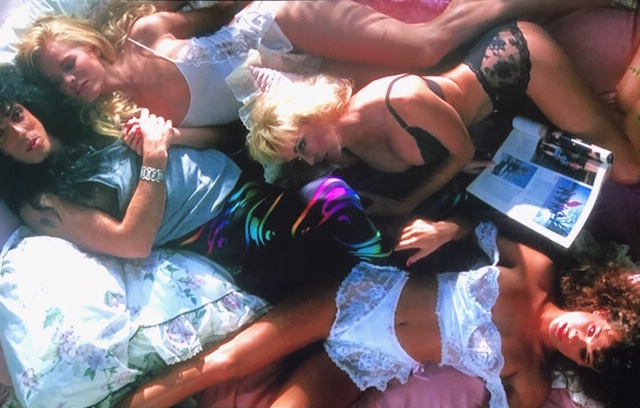 Paul Stanley lying on his bed with three half-naked models
