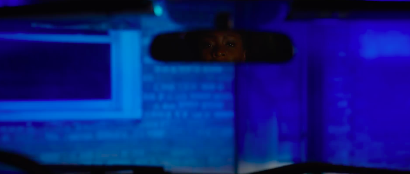 A still from 'Candyman' of Brianna looking into the cop's rearview mirror