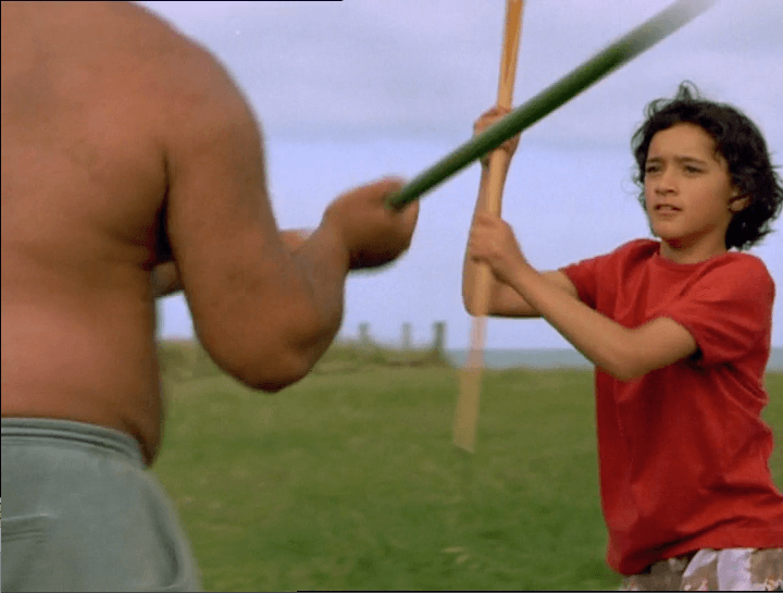 Pai is outside, training with her uncle with fighting sticks