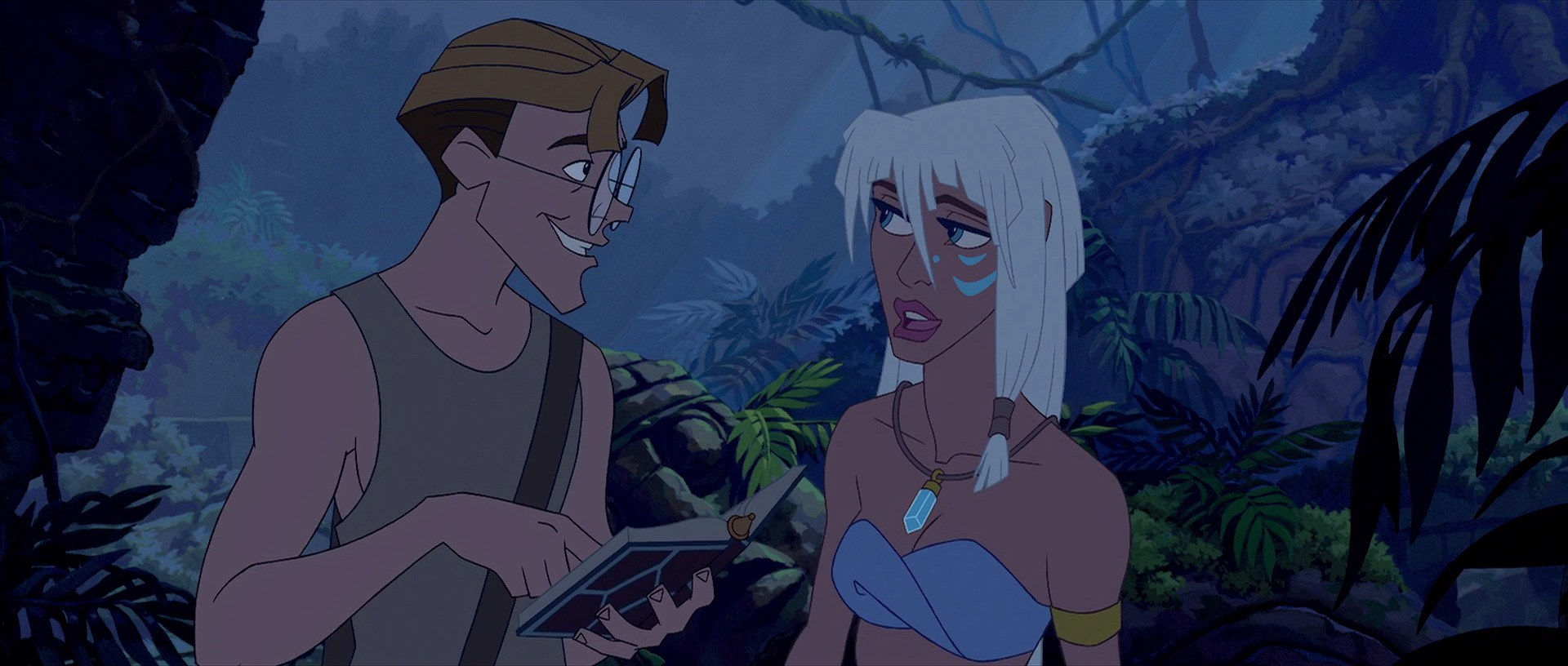 Milo and Kida stand in a jungle, smiling at each other. Milo holds a book.