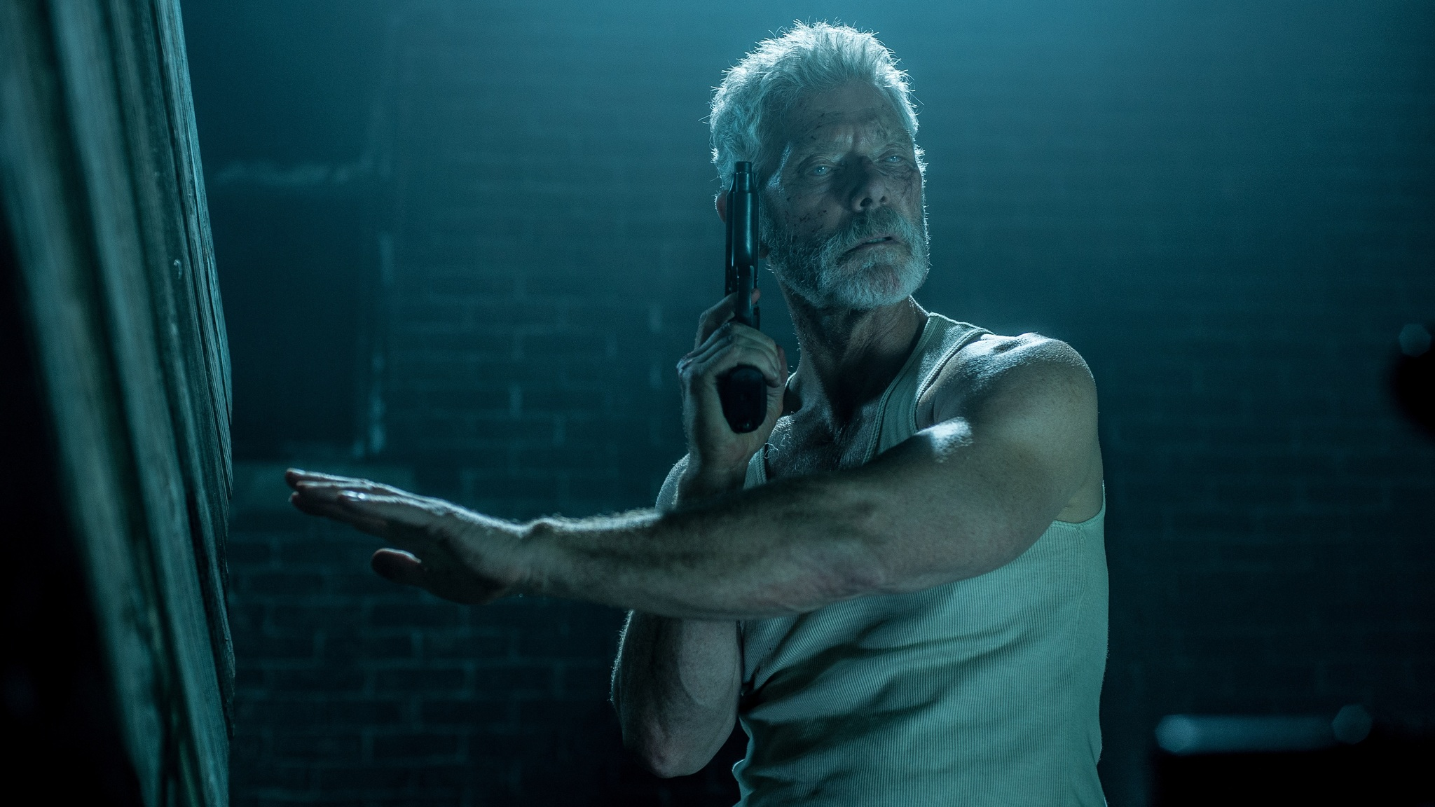 """A still from """"Don't Breathe"""" of Nordstrom with a gun in the dark"""