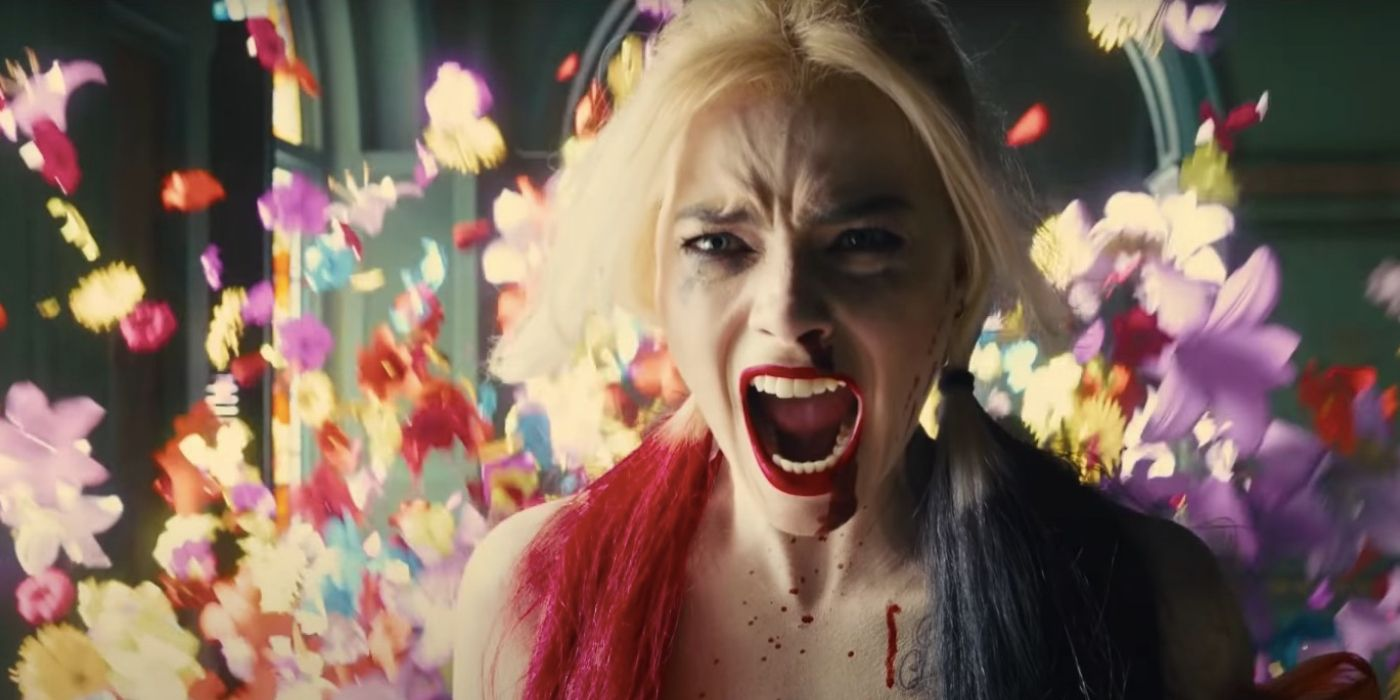 """A still from """"The Suicide Squad"""" of Harley Quinn screaming, flowers in the background"""
