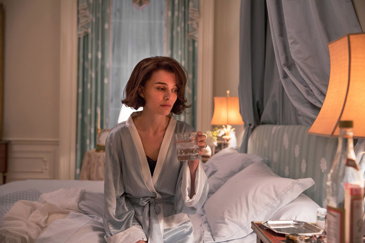 """A still from """"Jackie"""" of Natalie Portman as Jackie in her bedroom, sipping alcohol"""