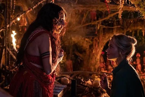 """A still from """"Jungle Cruise"""" of Trader Sam talking to Lily"""