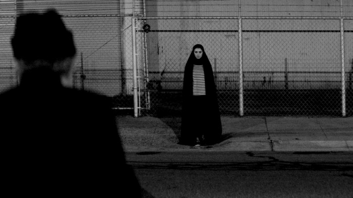 The Girl stands in the middle of the road, watching someone